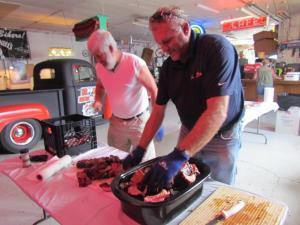 Gail Morgan and Rob Plendl cutting up the BBQ ribs to serve this evening